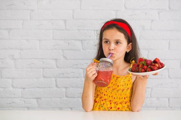 Girl drinking juice holding plate of strawberries