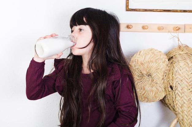 Девушка пьёт молоко из бутылки