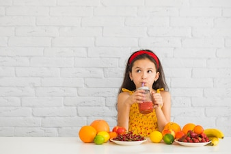 Girl drinking strawberry smoothies with colorful fruits on the desk
