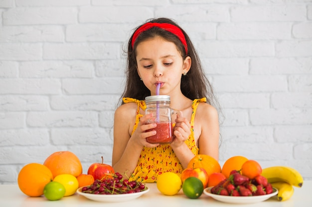 Girl drinking strawberry smoothies with colorful fruits