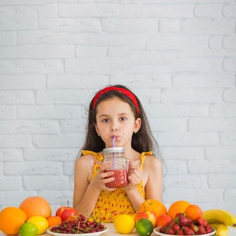 Girl drinking strawberry smoothies with ripe fruits over the desk