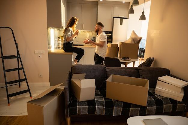 Девушка пьет чай и разговаривает со своим парнем дома. улыбаясь европейская пара. концепция переезда в новую квартиру. идея молодой семьи. картонные коробки с вещами. интерьер однокомнатной квартиры