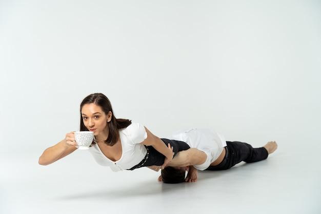 Девушка пьет чай во время акробатического трюка херд с мужчиной, изолированным на белом