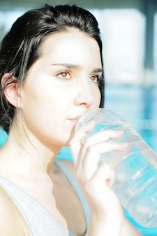Girl drinking water after fitness