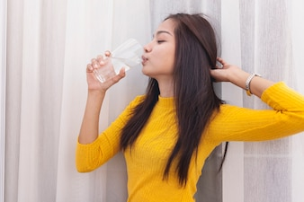 Girl drinking water and touching her hair