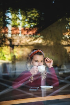 Girl drinks cappuccino in a coffee shop sitting at a table by the window.