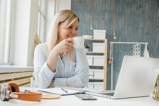 A girl drinks coffee at her desk