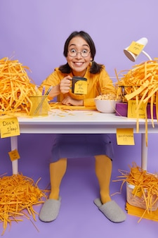 女の子はコーヒーを飲み、何をすべきかを覚えておくためにステッカーにメモをします紫色のオフィスの机に座って丸い光景を着ていますカジュアルな服はキャビネットで宿題をします