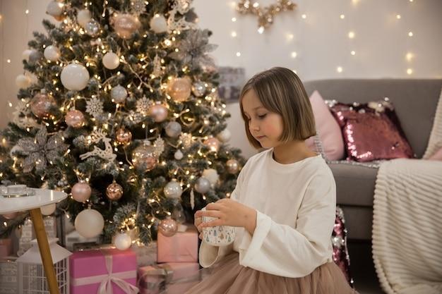 女の子はお祝いのリビングルームでマシュマロとコーヒーを飲みます