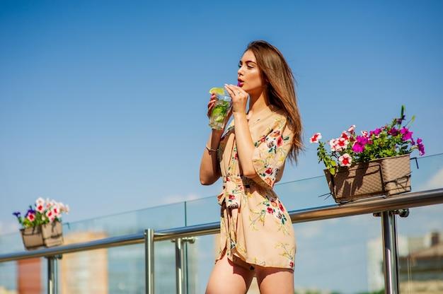 女の子は街を背景に暑くて蒸し暑い夏の日に氷で冷たいモヒートを飲みます。