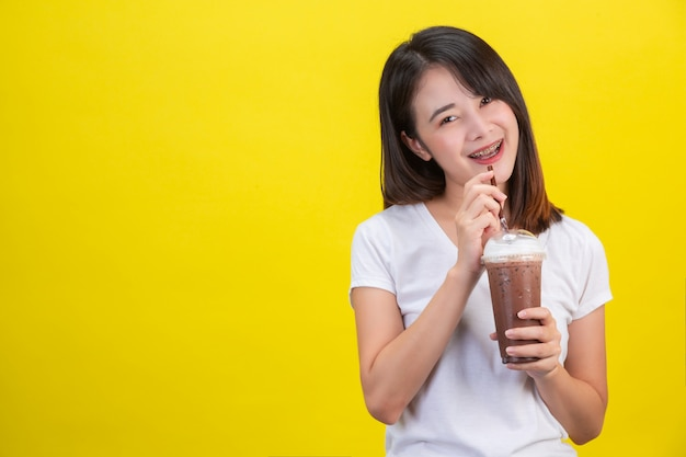 The girl drinks cold water from cocoa from a clear plastic glass on a yellow .