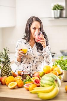 女の子は家でフレッシュジュースを飲み、目の前のキッチンの机で他の種類の果物を飲みます。