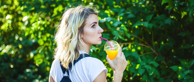 A girl drinks freshly squeezed juice, a healthy lifestyle banner concept.