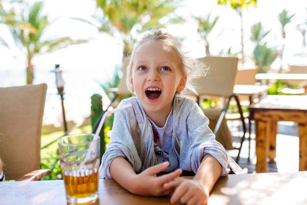 Девушка пьет фруктовый коктейль на фоне моря