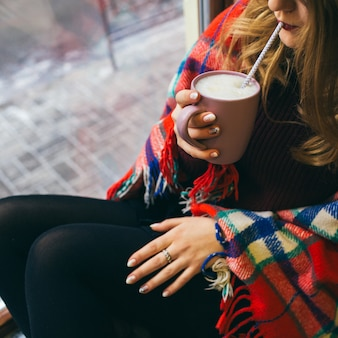 Girl drinks hot chocolate from cup sitting enveloped in plaid