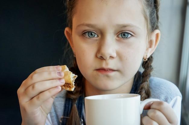 소녀는 자가 격리 중에 차를 마시고 쿠키를 먹습니다. 코비드-19 코로나바이러스. 집에있어 라