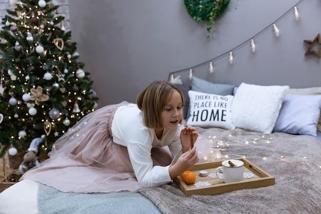 소녀는 축제 크리스마스 트리, 부드러운 초점 가운데 침실에서 차를 마시고 침대에서 먹는다