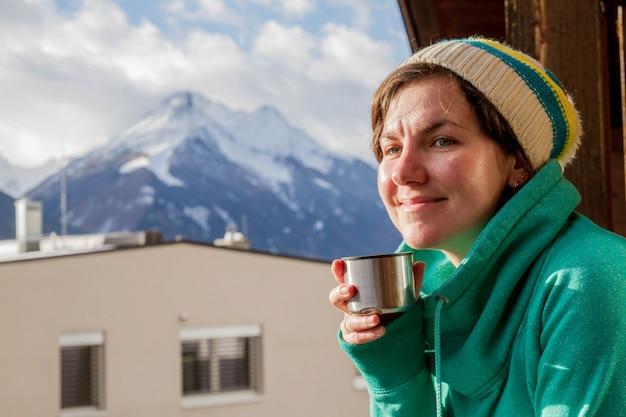 Девушка пьет чай и смотрит на горы