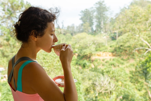 スリランカのジャングルの景色を眺めながらお茶を飲む女の子