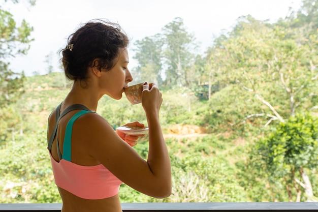 ジャングルの景色を眺めながらお茶を飲む女の子