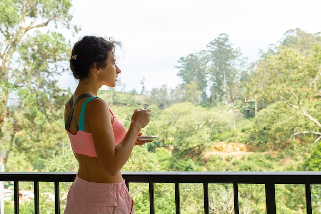 Girl drinks tea with a view of the jungle in sri lanka