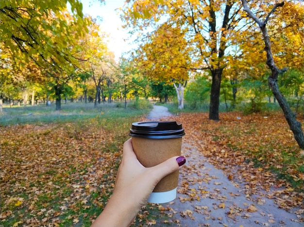 Girl drinks a warming hot drink while walking in the autumn in the park