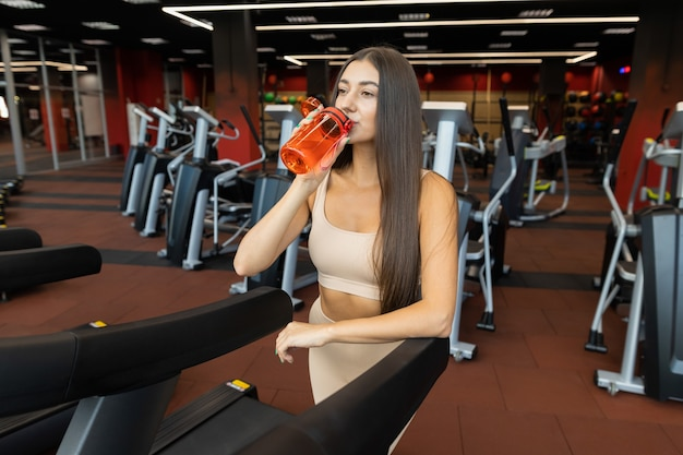 Girl drinks water from a shaker after exercising on a treadmill