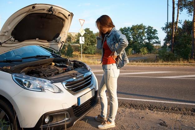 Girl driver next to a broken car with an open hood.