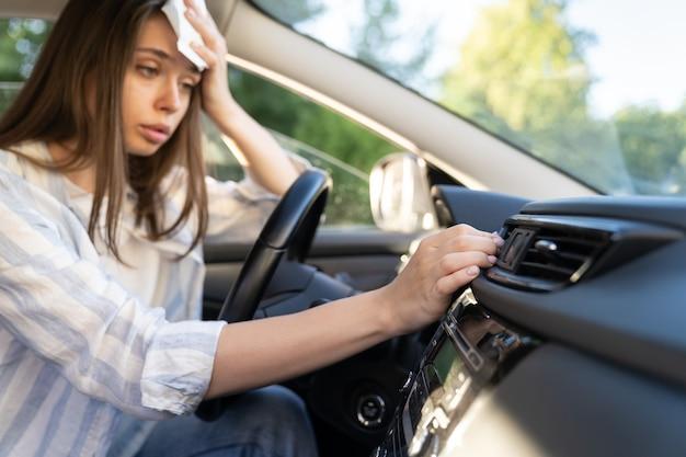 У девушки-водителя проблема с неработающей рукой кондиционера, проверяющей поток холодного воздуха, страдающего от жары