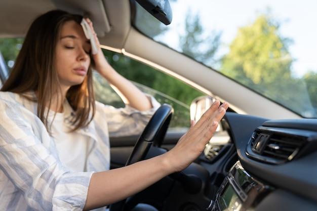 У девушки-водителя проблема с неработающей рукой кондиционера, которая проверяет поток холодного воздуха, страдающего от жары