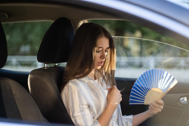 Девушка-водитель с ручным вентилятором, страдающая от жары в машине, имеет проблему с неработающим кондиционером