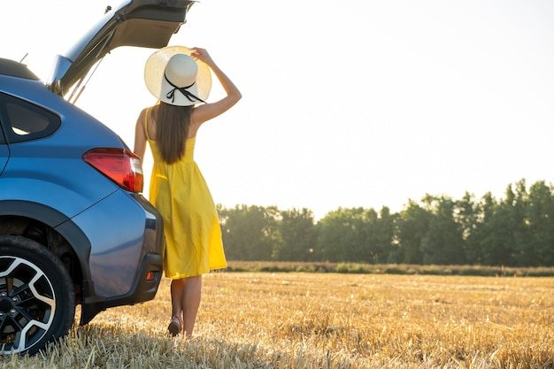 A girl driver in yellow summer dress and straw hat standing near a car enjoying warm summer day at sunrise. travel and vacation concept.