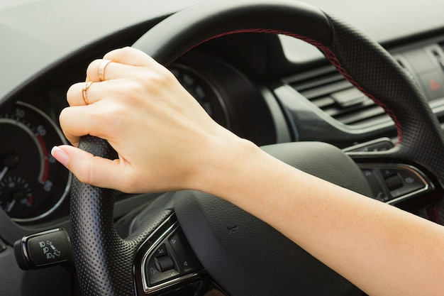 Girl drives a car, holds the steering wheel with one hand