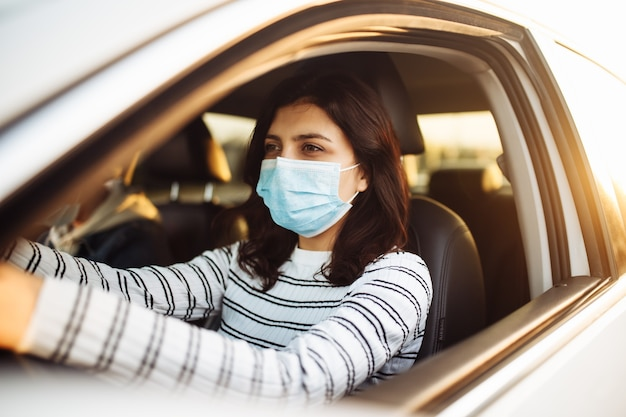 A girl drives a car with a passanger wearing medical mask during coronavirus pandemic quarantine