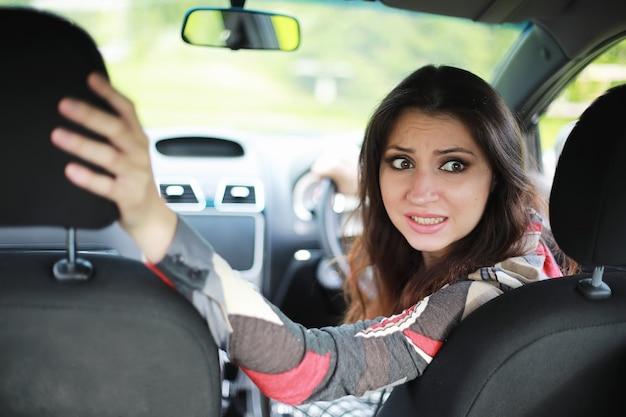 그녀의 얼굴에 차를 운전하는 소녀 나쁜 감정