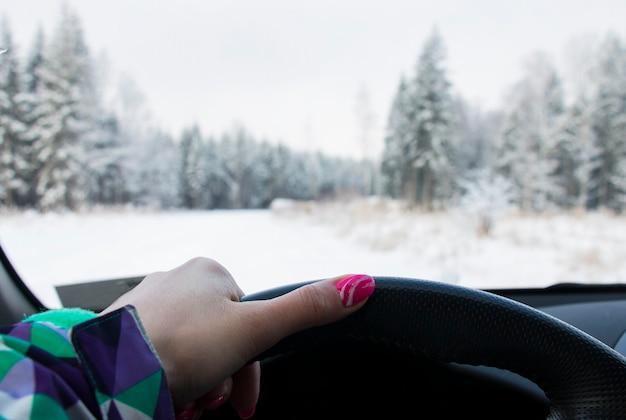 Девушка за рулем автомобиля в заснеженном лесу