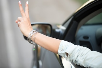 Girl driving and showing the victory gesture