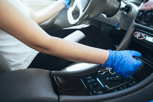 車の中で手袋とマスクを持って運転している女の子。コロナウイルスパンデミック。