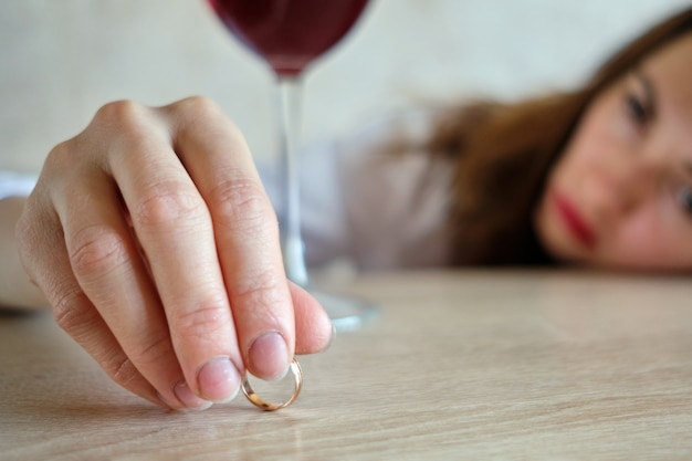 The girl drunk from wine lies her head on the table after losing her job.