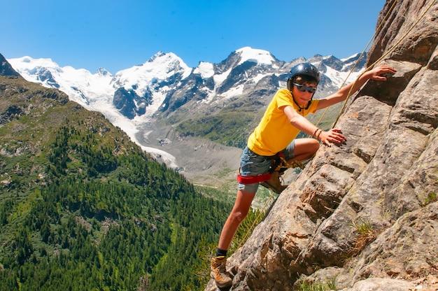 Девушка во время курса скалолазания в высоких горах