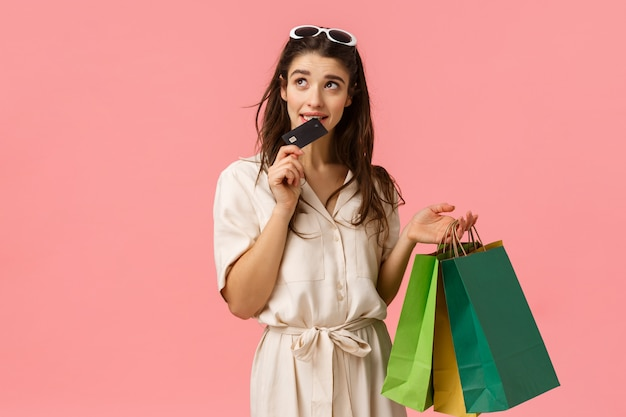 Girl eager waste more money feeling guilty biting credit card and looking thoughtful hesitant up, thinking, trying stop buying new things, shoppaholic holding shopping bags, pink background