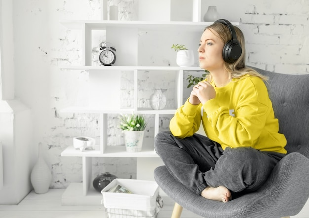 Girl in earphones in yellow blouse sits relax on grey couch to listen music or online courses, dreaming or recalling great moments. white brick wall background.