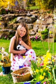 Girl on easter egg hunt with living easter bunny
