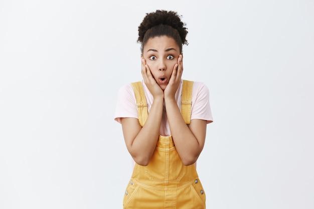 Девушку легко поразить шокирующими слухами. портрет впечатленной, изумленной и удивленной студентки-афроамериканки в желтом комбинезоне с зачесанными вьющимися волосами, задыхающейся от потрясения и смотрящей изумленно