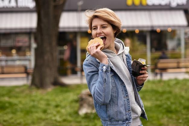 패스트 푸드와 함께 햄버거를 먹는 여자