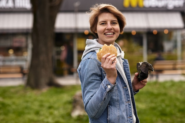 패스트 푸드와 함께 햄버거를 먹는 소녀