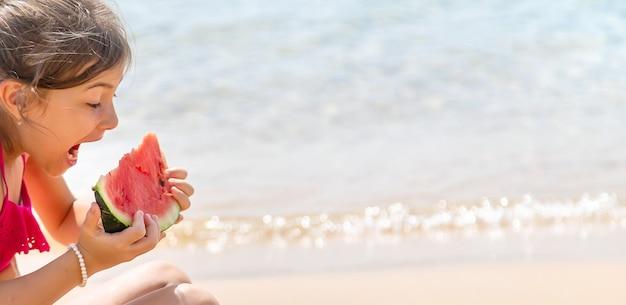 ビーチでスイカを食べる女の子