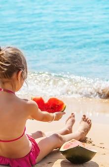 ビーチのトップビューの砂の上でスイカを食べる女の子
