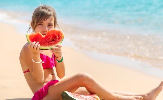 ビーチの砂の上でスイカを食べる女の子