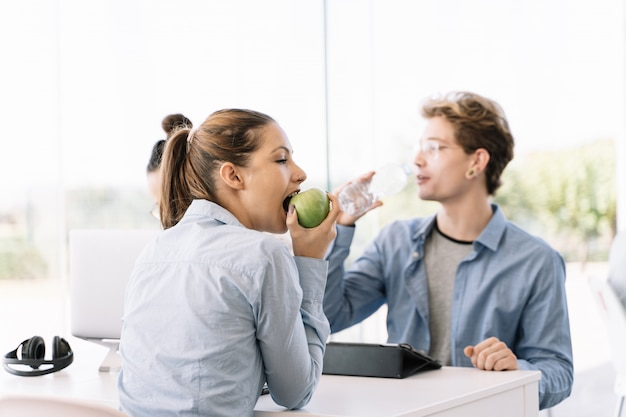 Girl eating apple at a table with other people